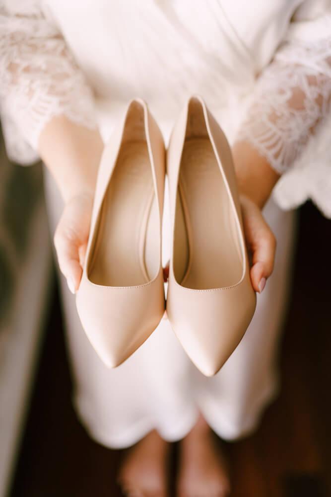 bride wedding dress holds highheeled shoes her hands 1
