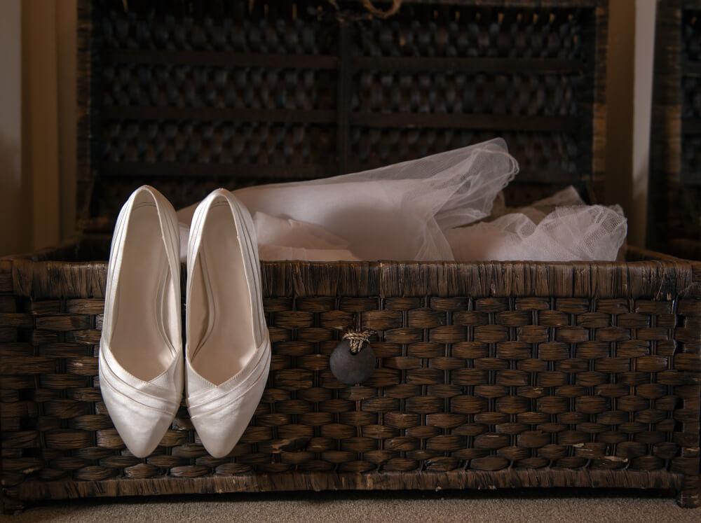 white silk wedding shoes heels bride near wicker suitcase violet flower