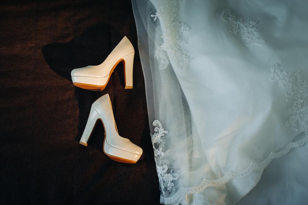 white wedding shoes dress black background
